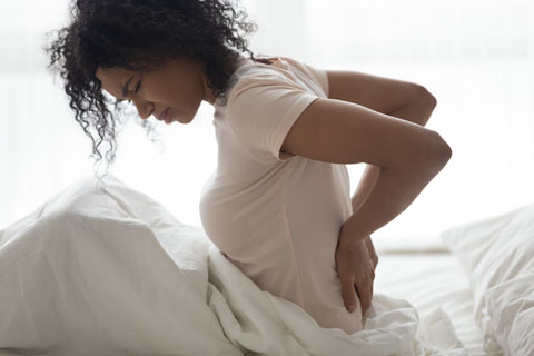 Women in bed holding back in pain